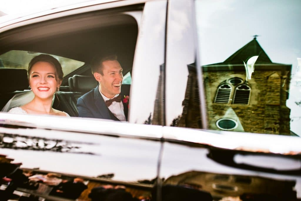 bride and groom laughing inside a RollsRoyce vintage car after they got married at St. George's-in-the-Pines Anglican Church in Banff National Park