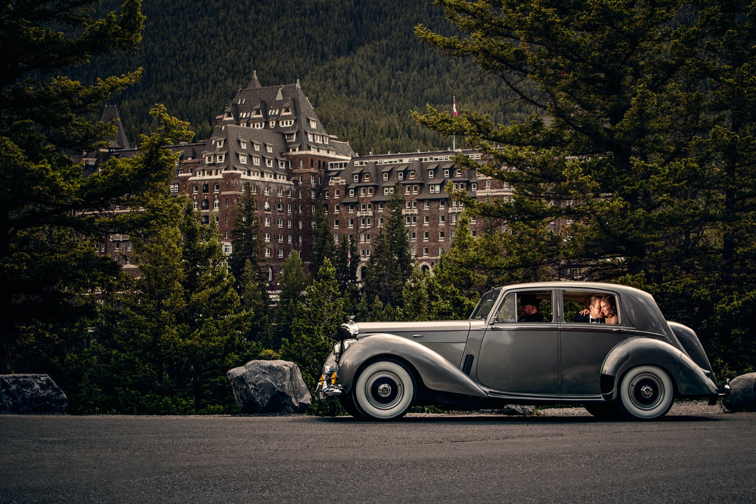 The Banff Springs Hotel with a bride and groom inside a luxury Bentley vehicle