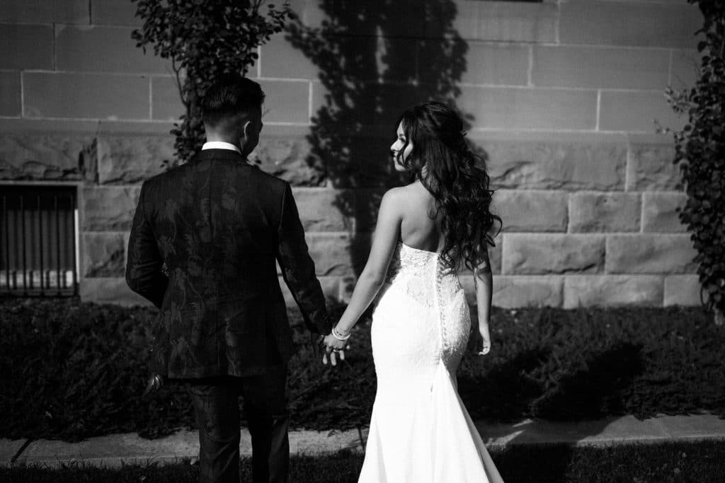 Bride and groom walking downtown Calgary holding hands photographed by Calgary wedding photographers