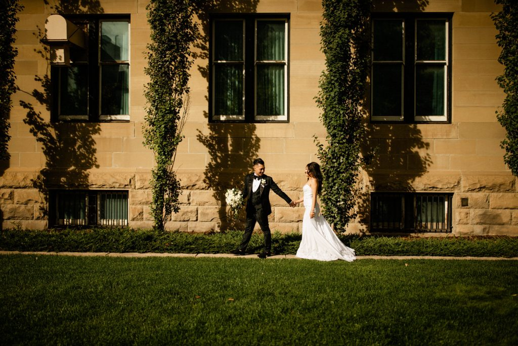 Bride and groom walking hand in hand in Calgary photographed by Calgary wedding photographers