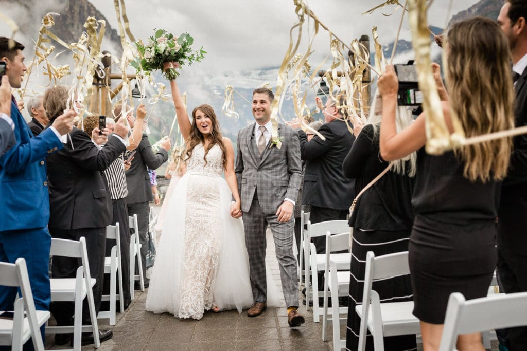 Ribbon tassels waved by guests at a Lake Louise ceremony with the bride and groom walking down the aisle, laughing with happiness.