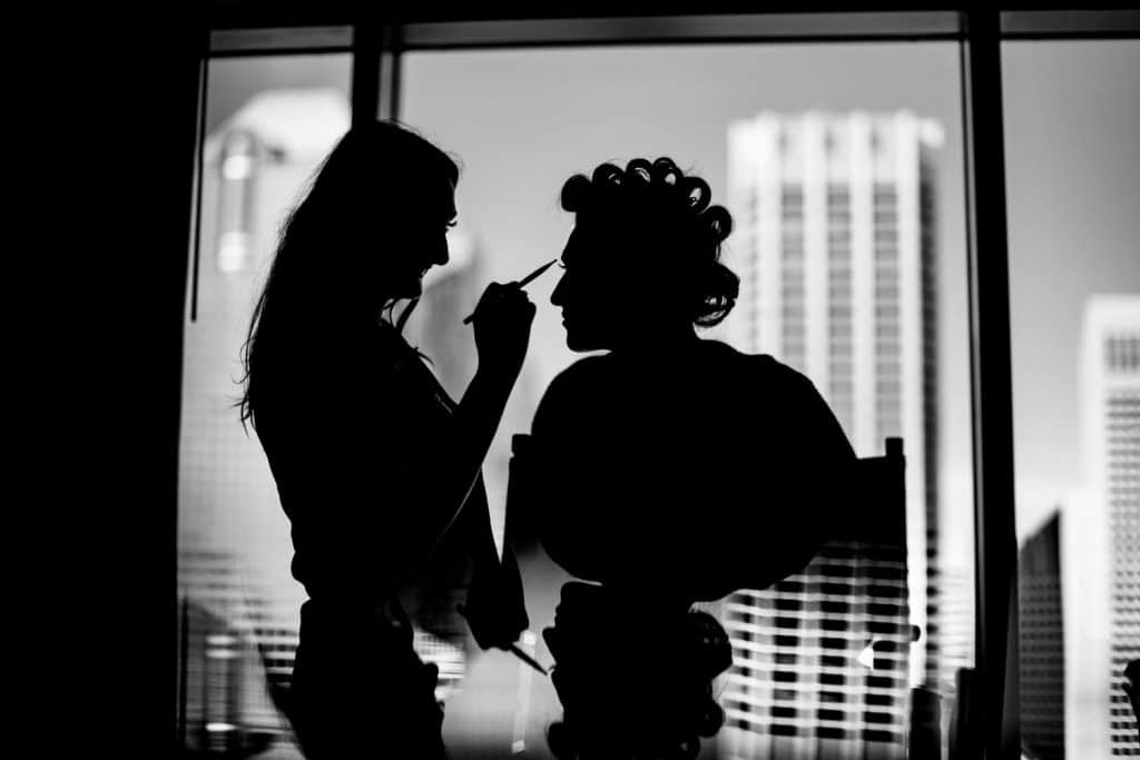 Bride getting ready with her makeup artist as the Calgary bride gets ready at the Hyatt Hotel