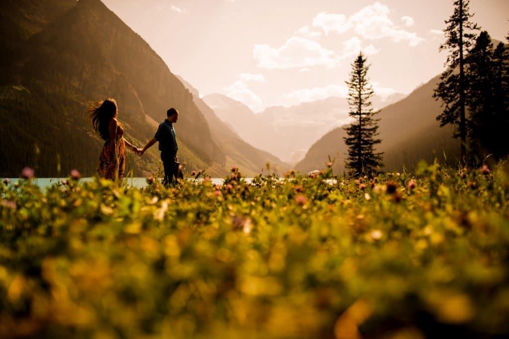 Warm summer evening engagement shoot at Lake Louise as the couple walk toward Victoria Glacier