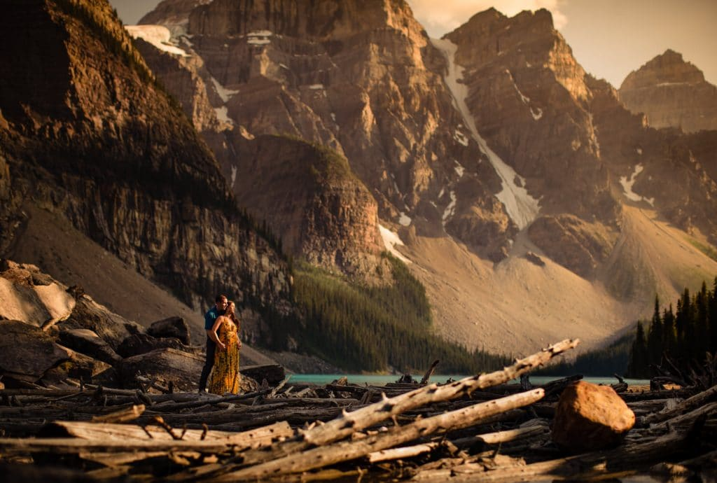 The Valley of The Ten Peaks in the background of a couple enjoying Moraine Lake