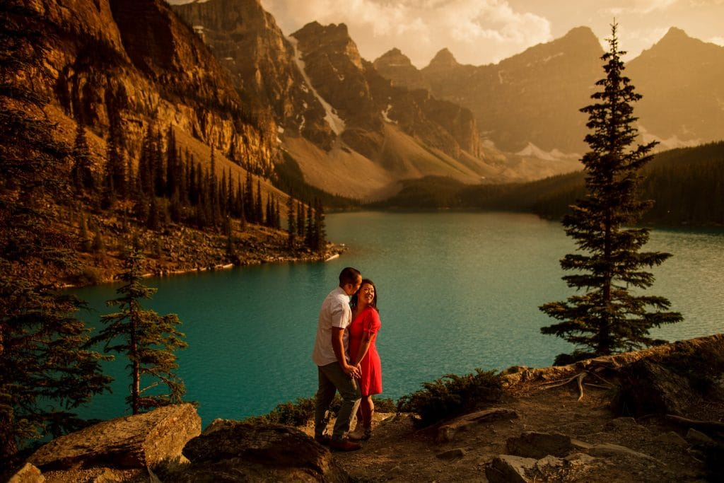 engagement shoot at Moraine Lake with the lady in red dress and her partner holding her