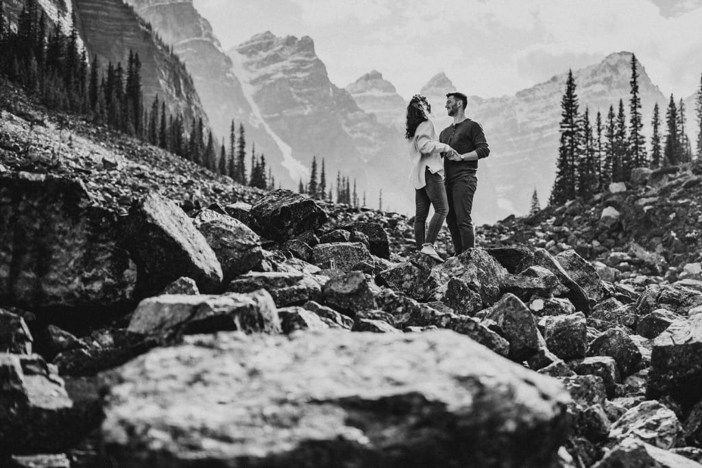 Black and white photograph of a couple surrounded by Moraine Lake and The Valley Of The Ten Peaks