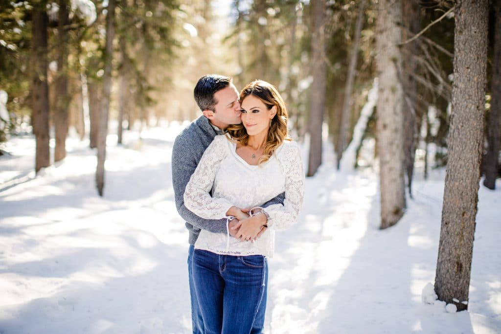 engagement Lake Louise wooded area with a portrait of a couple holding each other in the winter with snow around them