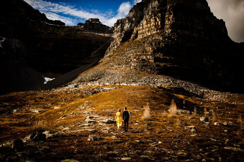 engaged couple walk on a gorgeous Fall and Autumn day in the Valley of The Ten Peaks by Moraine Lake The Canadian Rockies