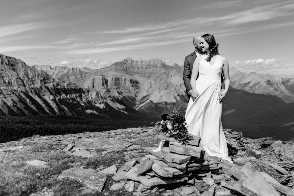 A photo of a bride and groom at the top of a Canmore Mountain