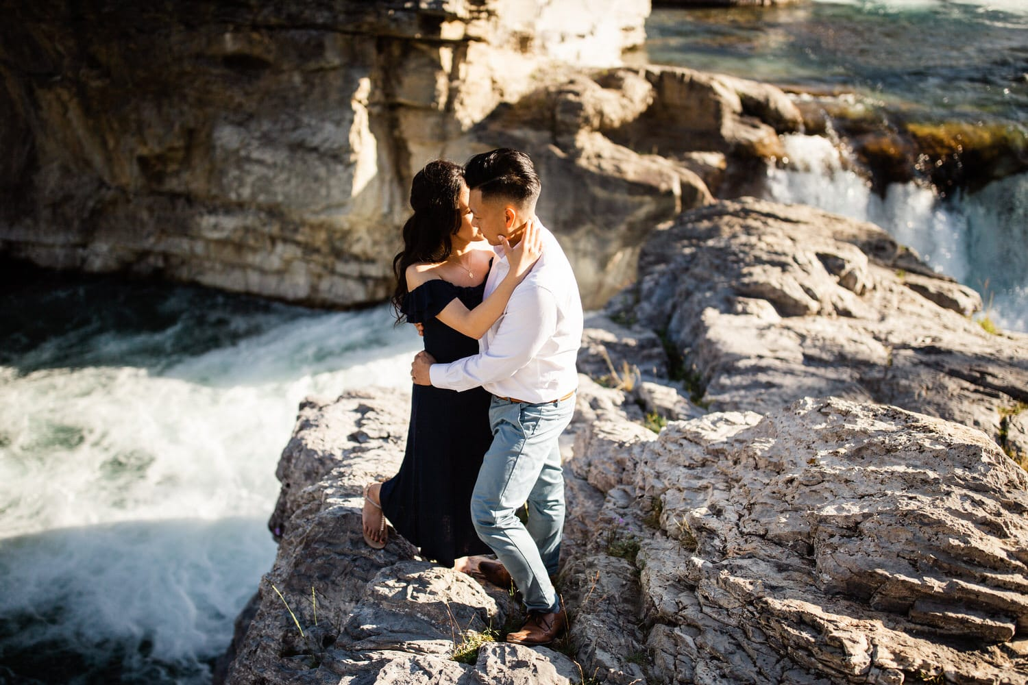 Candid engagement photo of a couple embracing at Elbow Falls in Kananaskis