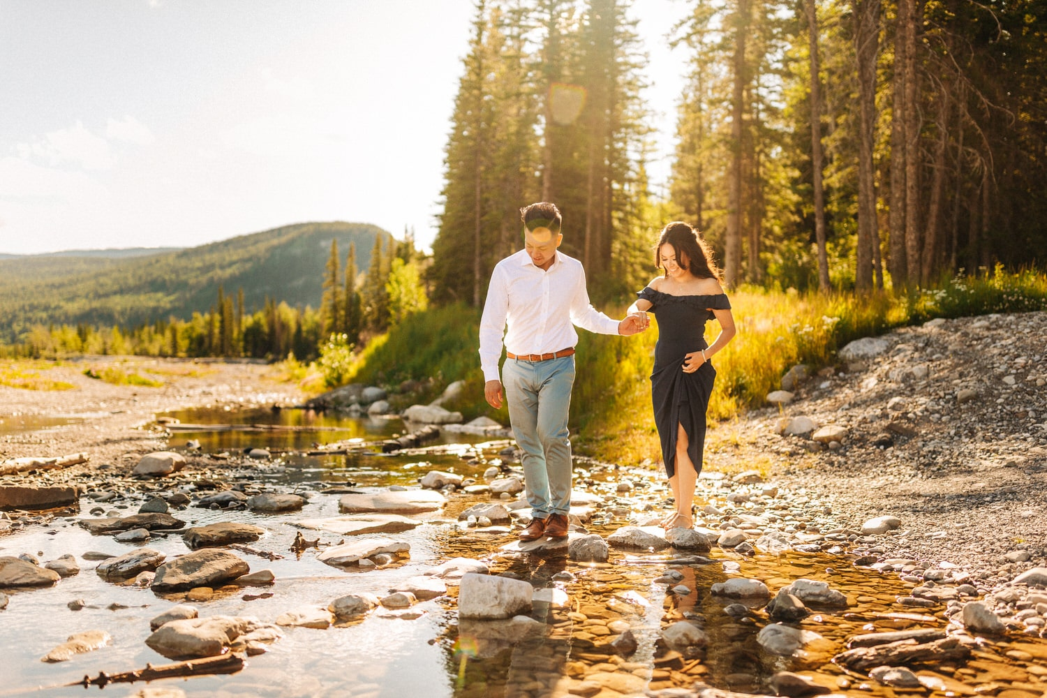 Elbow Falls Engagement Photo of a Couple Walking On the Rocks