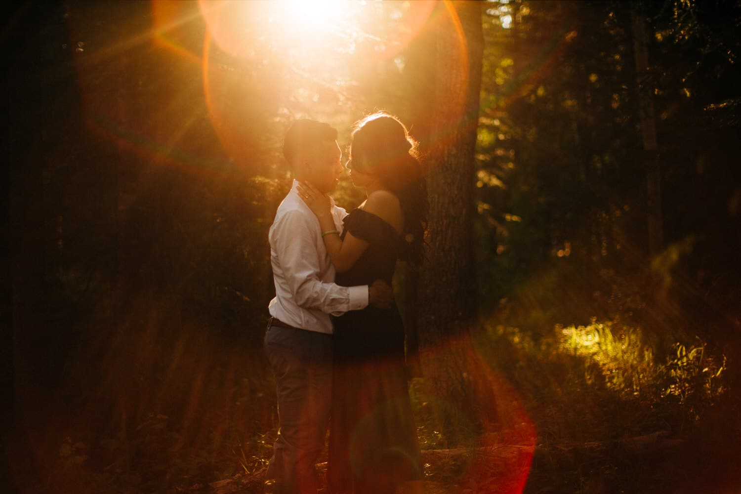 Kananaskis Engagement Photos in the woods with back lighting through the trees