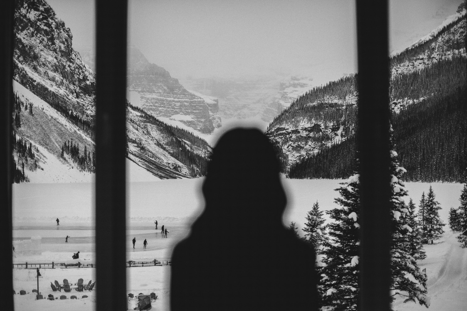 Bride looking out the window of Chateau Lake Louise and the frozen Lake Louise lake