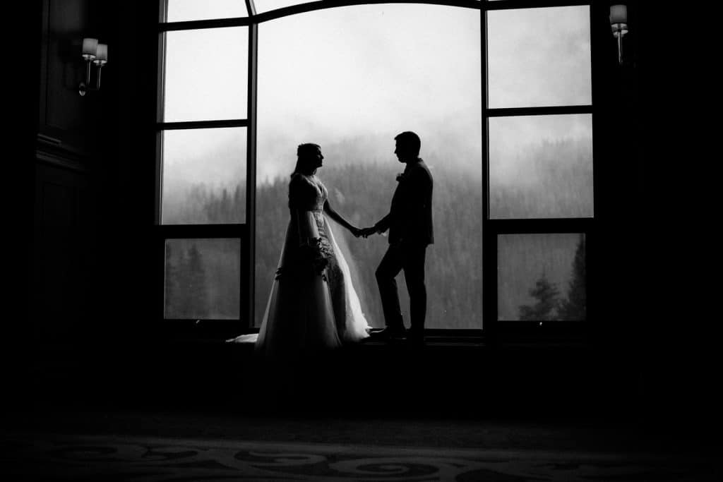 Bride and groom holding each other at the Chateau Lake Louise Hotel beside the big grand windows that overlook Lake Louise