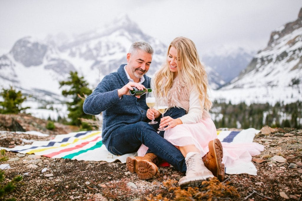 Engagement couple celebrating their love for each other after being flow by Alpine Helicopter in Canmore to a Marvel Pass
