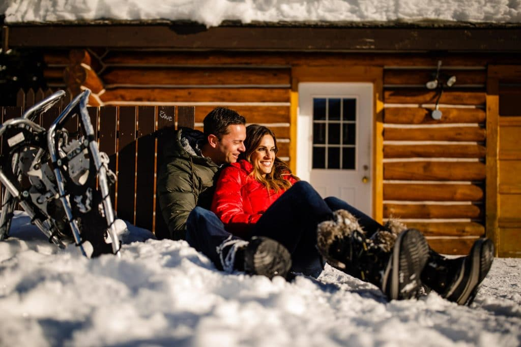 engagement photograph of an engaged couple at Lake Louise boat house sitting hugging and laughing together