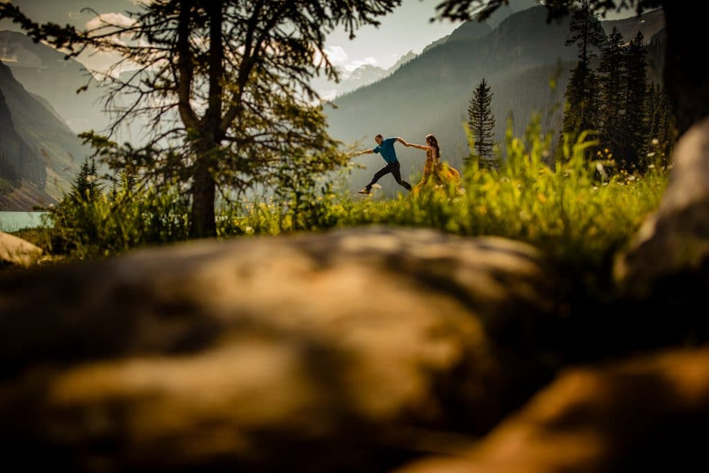 A couple run and jump in the air by Lake Louise