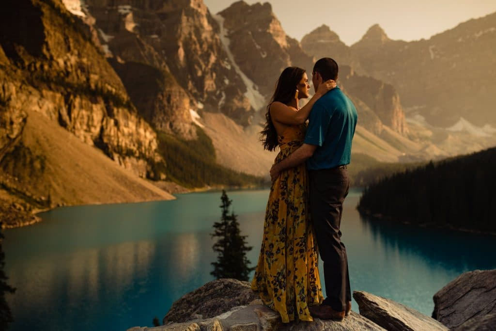 a portrait of a couple holding each other at Moraine Lake at sunset