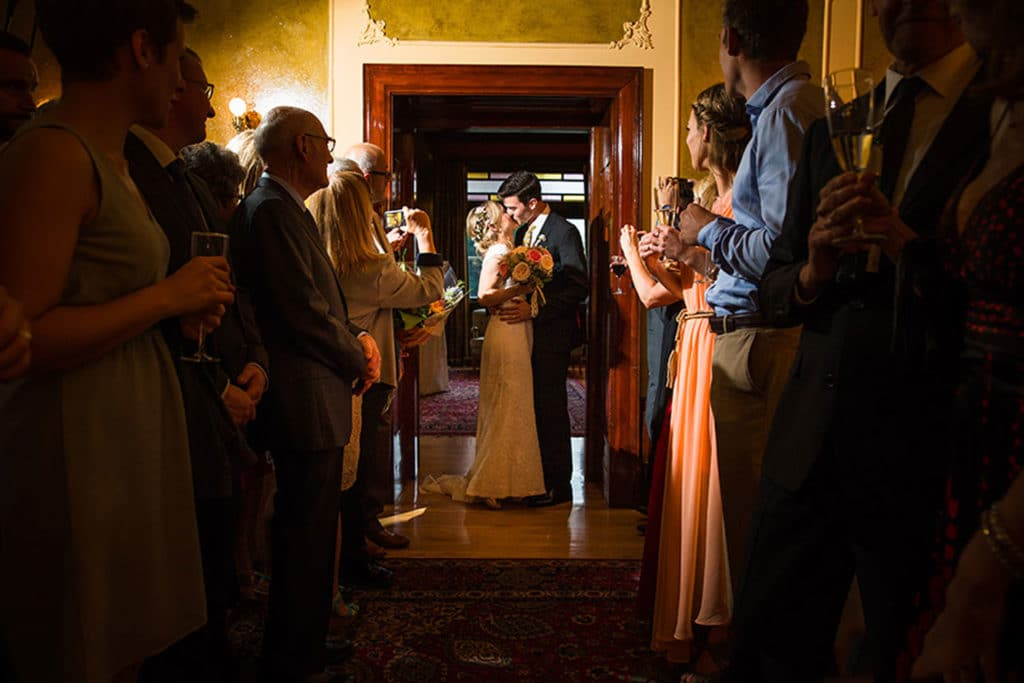 A bride and groom kissing the Lougheed House before the reception grand entrance