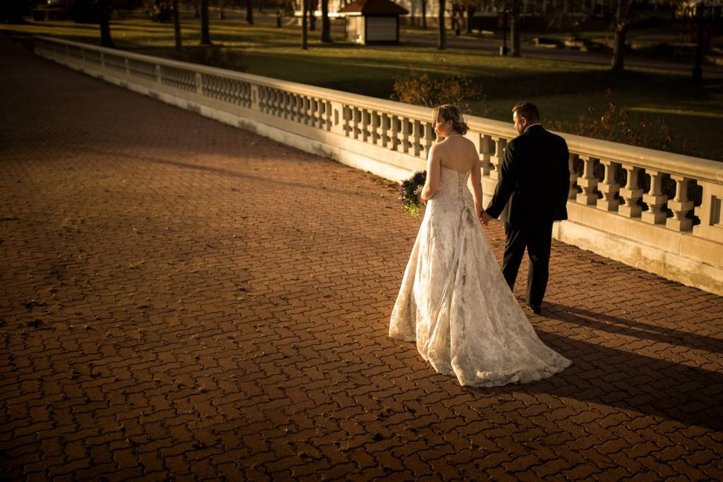 A bride and groom walking during the sunset at Spruce Meadows
