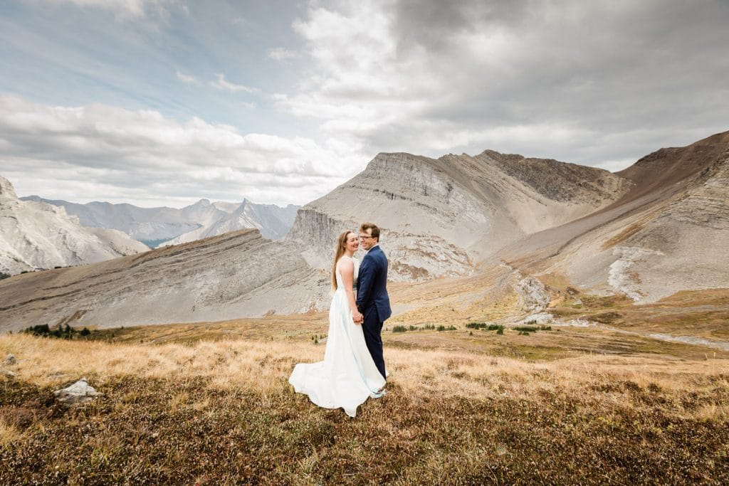 Bride and Groom laughing together as they enjoy the helicopter mountain elopement experience outside of Canmore Alberta