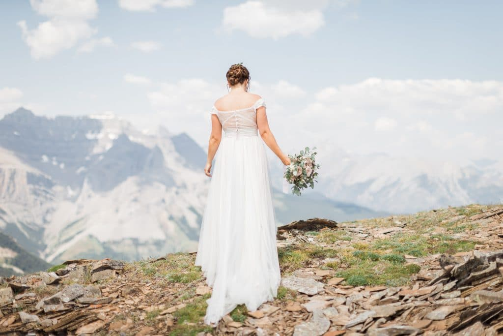 A bride is walking away from the camera holding flowers as the bride walks towards Cascade Mountain in the distance