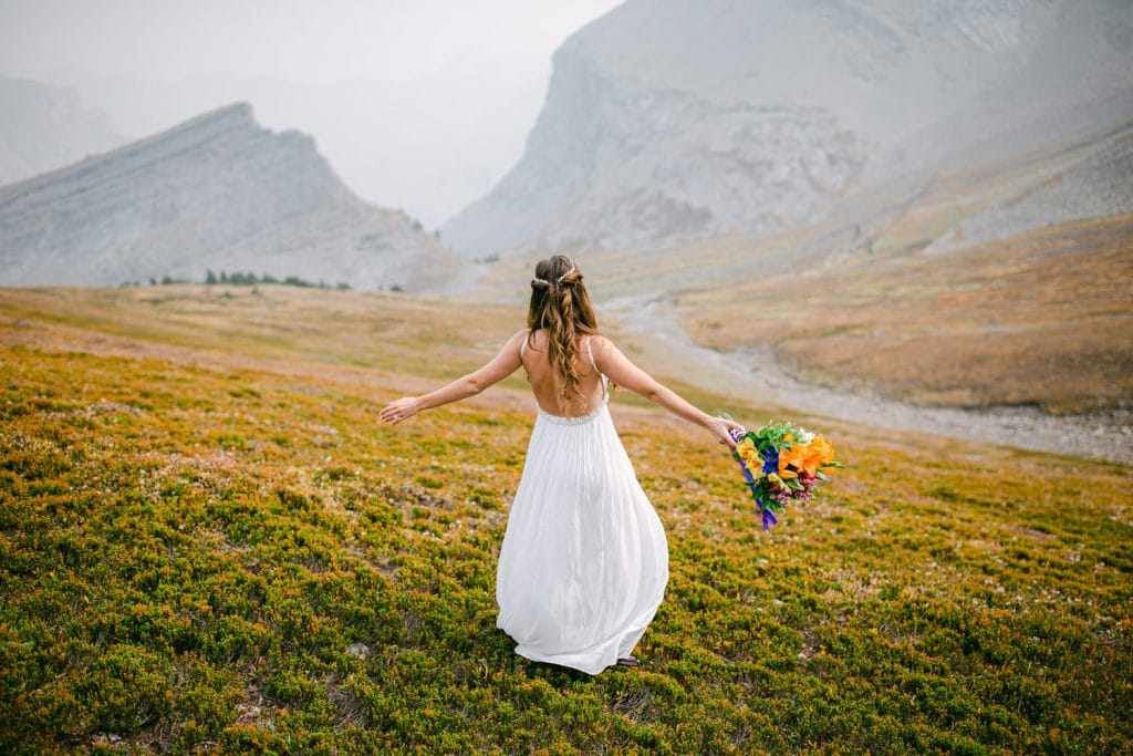 Helicopter elopement wedding with a bride dancing and enjoying the mountains photographed by Canmore adventure wedding photographer