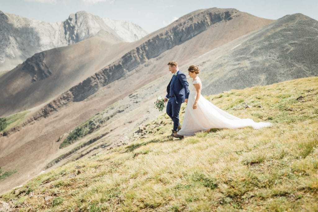 Adventure wedding photograph of a bride and groom walking towards their elopement wedding location during their helicopter wedding adventure