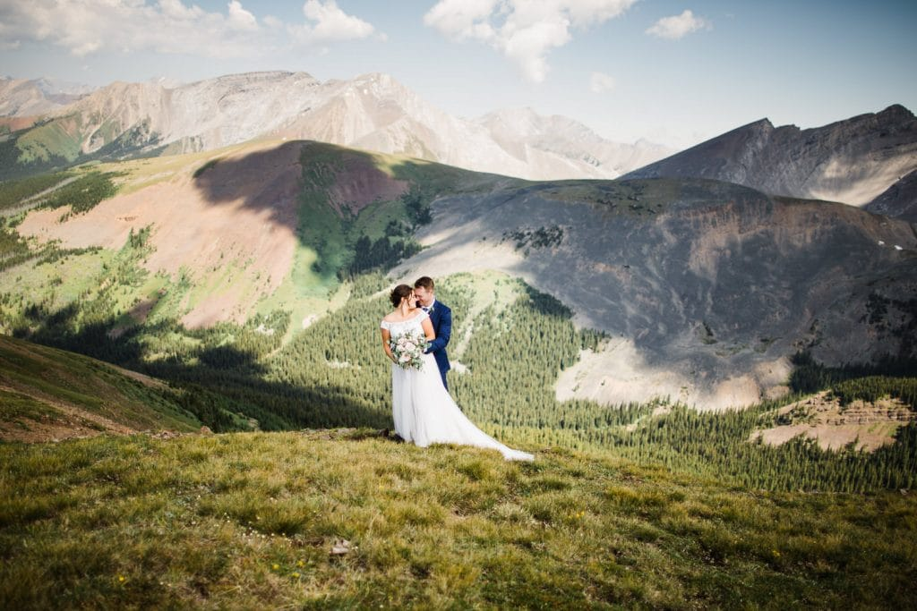 Banff helicopter elopement photograph with the bride and groom holding each other at the top of a mountain