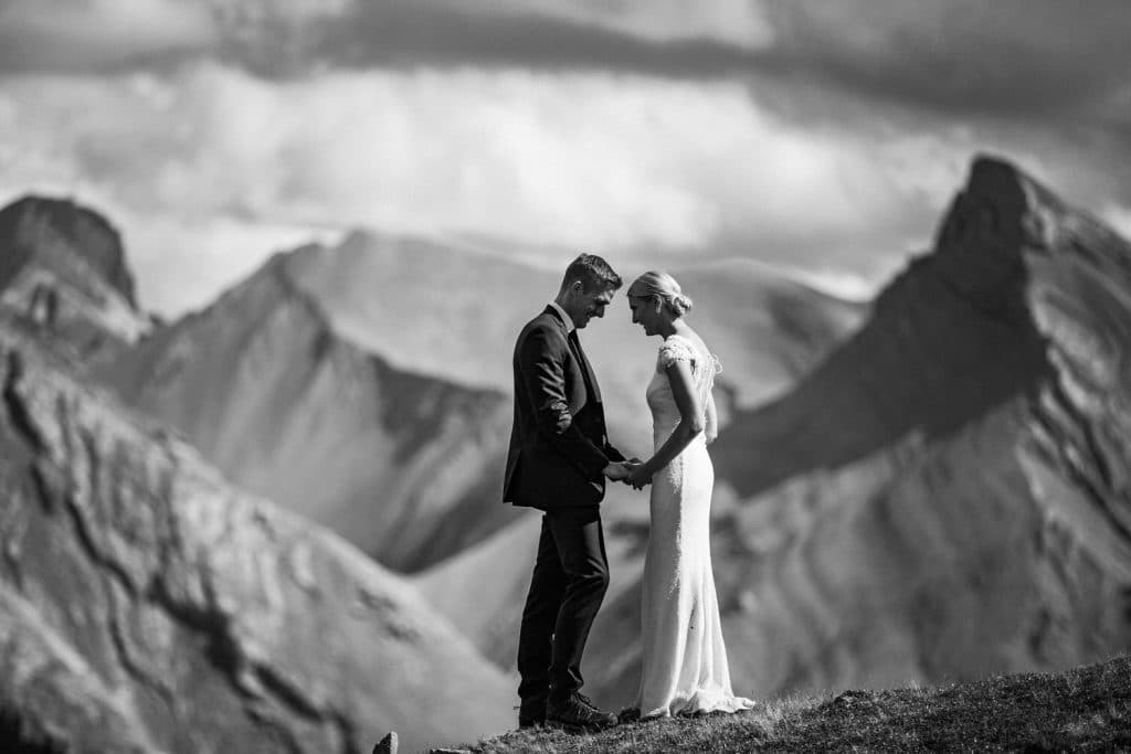 A bride and groom holding hands during their elopement wedding with the mountains behind them