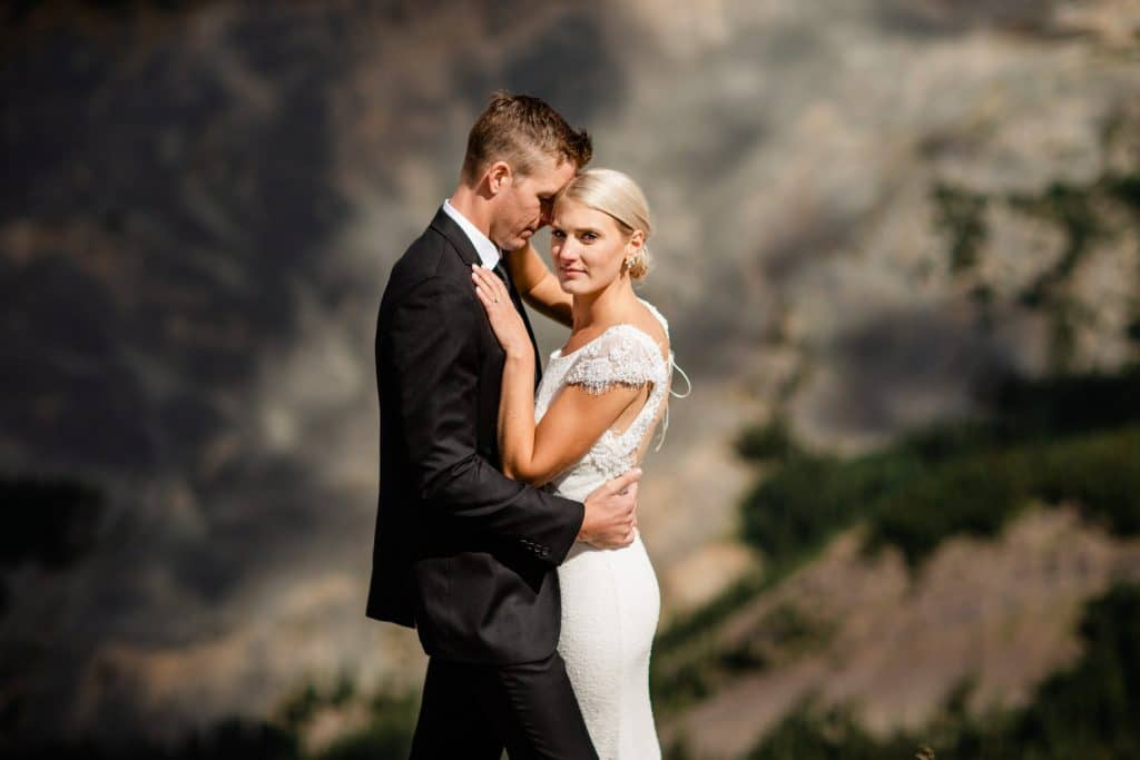 Mountain top Canmore wedding with a Bride holding her groom after they got married via a helicopter ride in Canmore