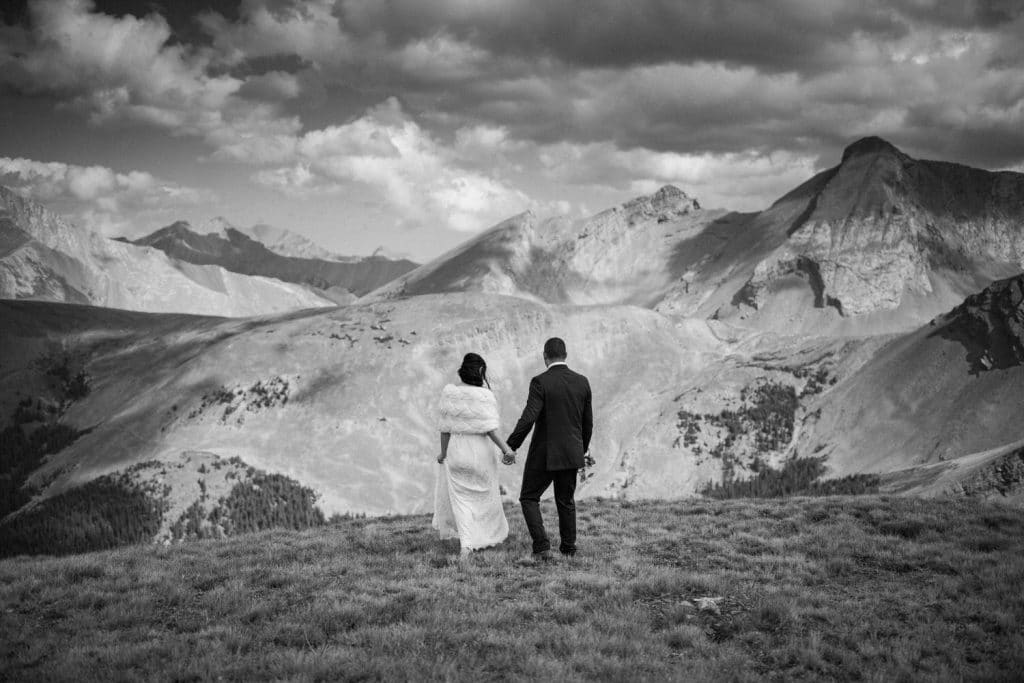 Adventure photographer photographs a moment between the groom and bride as they walk towards their elopement ceremony