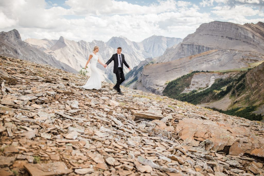 A helicopter mountain adventure elopement with a bride and groom walking down the mountain outside of Canmore Alberta