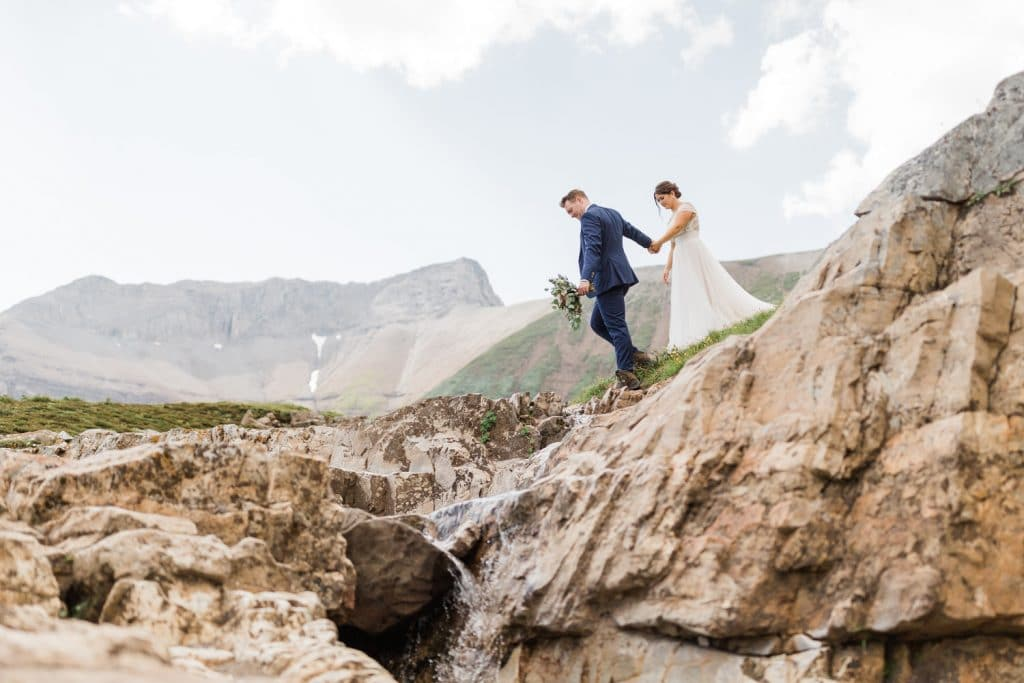 A couple walking in the mountains after being dropped off by Alpine Helicopters in Banff National Park Heli wedding experience.
