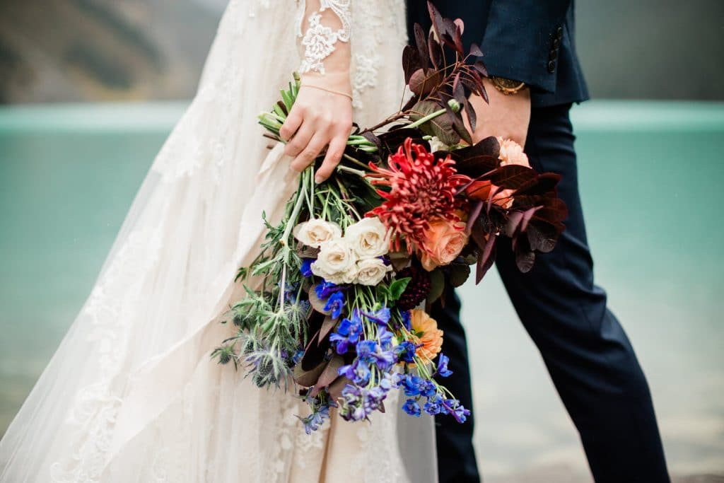Bride holding flowers at Chateau Lake Louise as she connects with her partner
