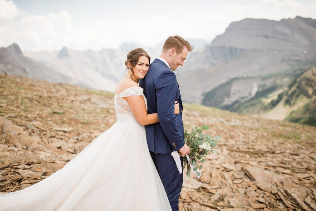 A bride holding the back of her groom after hiking down a Canmore mountain from their helicopter wedding elopement