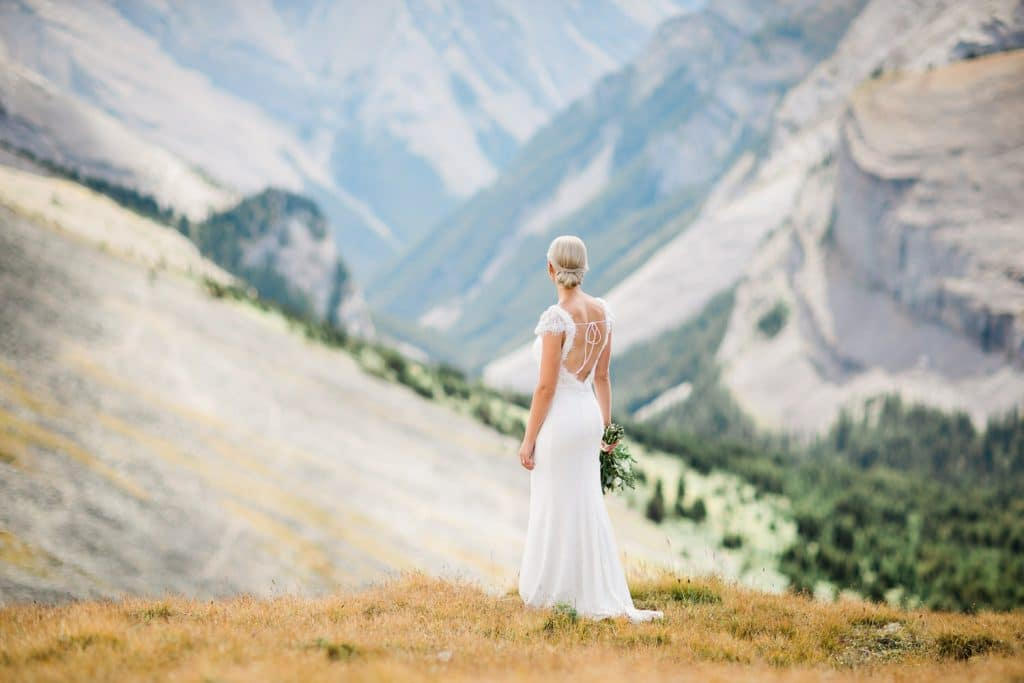 A portrait of a bride looking down the valley after landing for her mountain top Canmore helicopter elopement photographed by Geoff Wilkings Photography Canmore's premiere wedding photographer