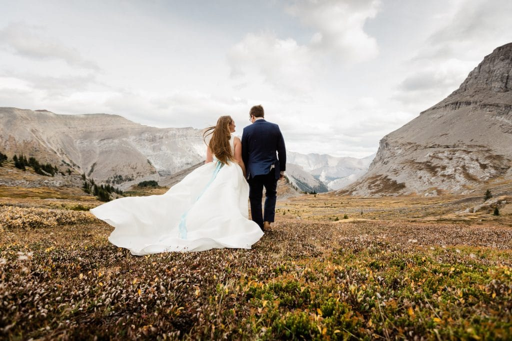 Windy day during a all and autumn mountain alpine elopement wedding with a bride and groom walking down the mountain holding hands photographed by Canmore wedding photographer
