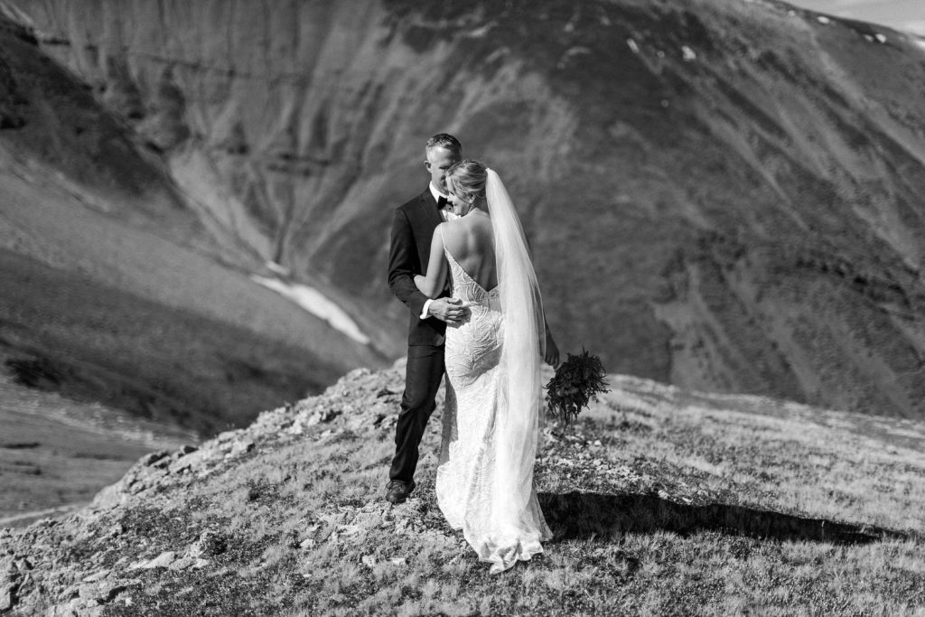 Banff National Park elopement wedding photographer captures a moment between a bride and groom after their wedding ceremony via a helicopter