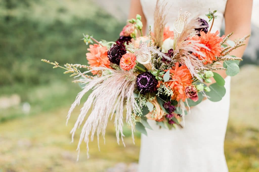 Flowers made in Canmore and are being held by a bride from a mountain helicopter wedding