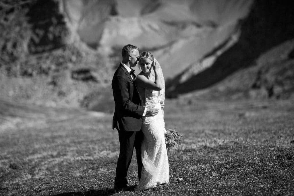 Walking down the alpine meadows after getting married from a helicopter mountain elopement Canmore Alberta