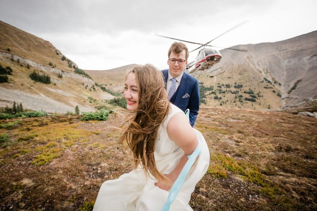 Bride groom laughing as the helicopter lands from their helicopter mountain wedding photography shoot