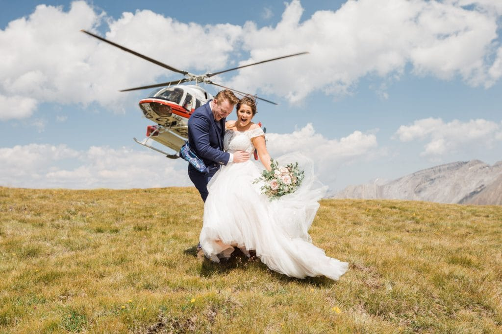 Helicopter mountain elopement photography wedding with a bride and groom laughing as the private alpine helicopter takes off and creates wind from the downdraft lifting the dress of the bride