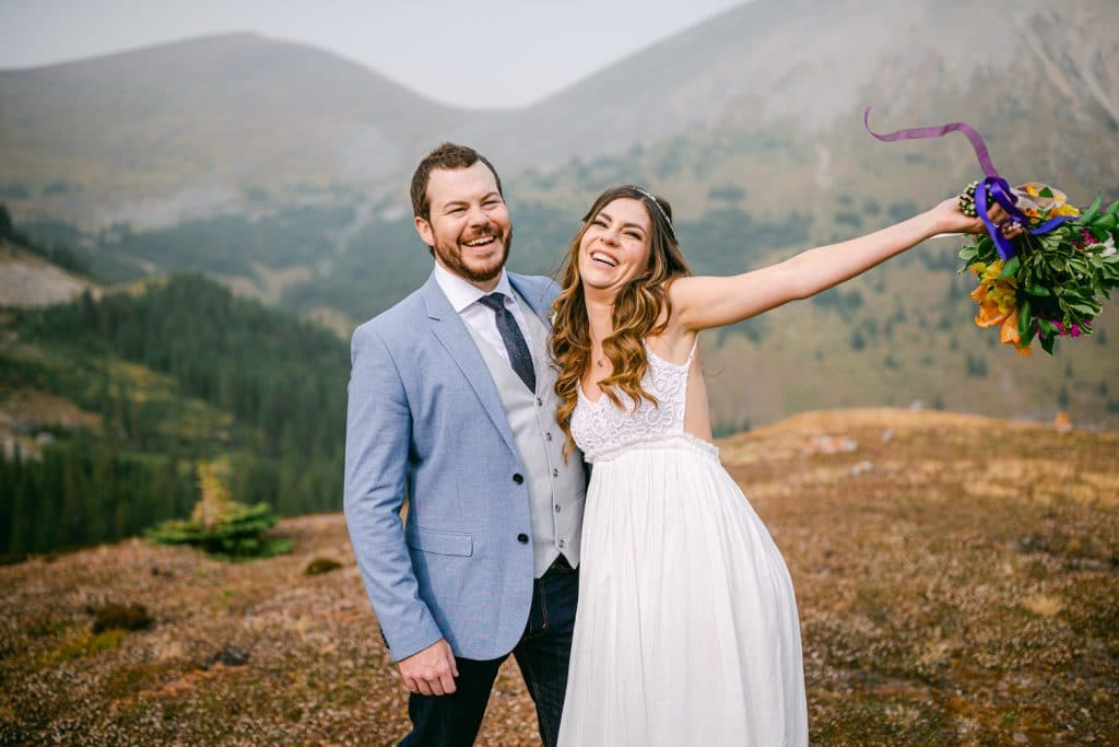 A fun photograph of a bride and groom laughing as they wait for the helicopter from Canmore to pick them up.