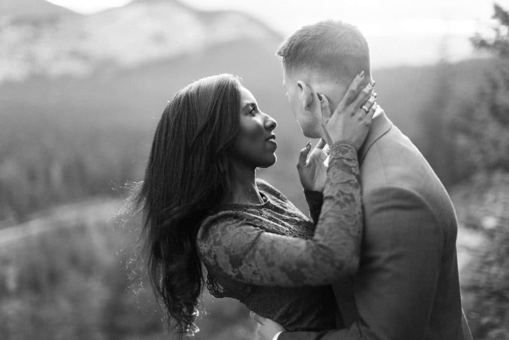 Banff engagement photographer engagement photos capturing two people close and in love with Sulphur Mountain in the background