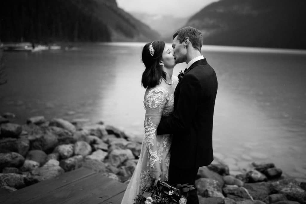 Lake Louise wedding photograph of a bride and groom kissing romantically by Lake Louise shoreline