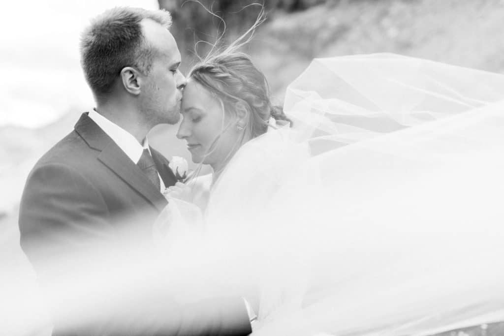 Groom kissing his bride during their adventure mountain wedding in Canmore Alberta