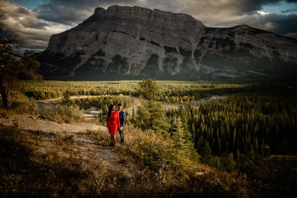 Engagement shoot in Banff with an engaged couple holding each other close to Mount Rundle