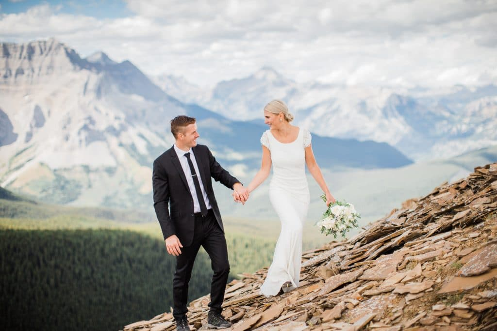 Bride and groom walking together after being their private mountain top helicopter mountain elopement in Banff National Park