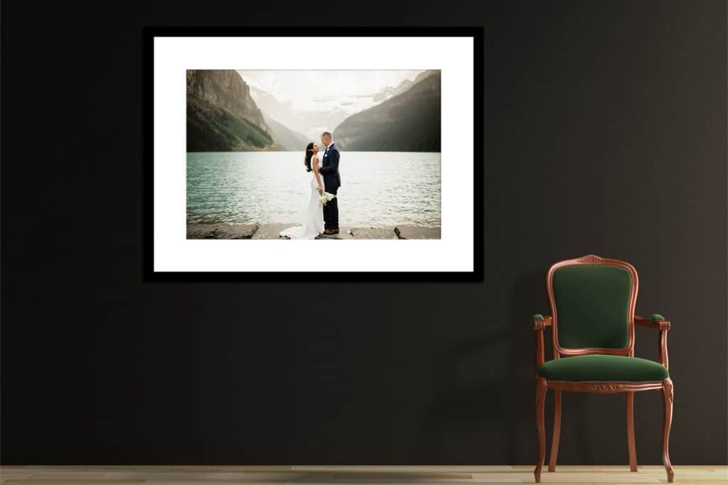 A couple looking at each other on the shoreline in Lake Louise after their elopement hung as wall art in their home